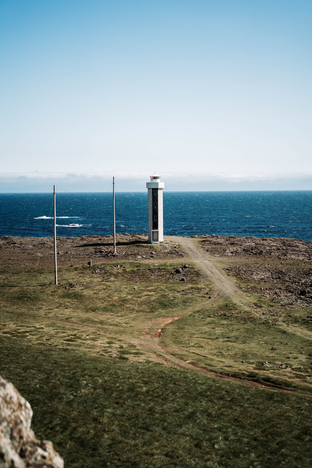 white and black lighthouse on green field near blue sea under blue and white sky during daytime
