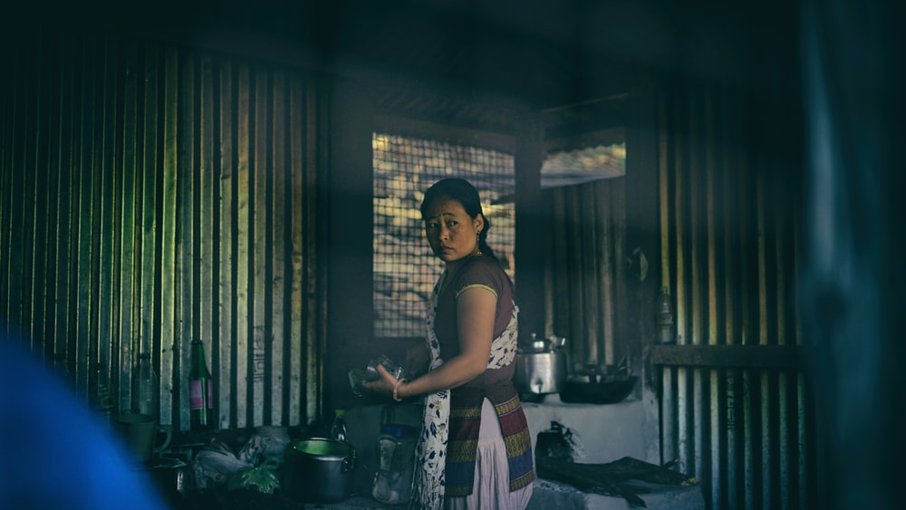 woman in apron standing near cooking pots