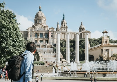 people near museu nacional d'art de catalunya in barcelona under blue and white sky during daytime neoclassical zoom background