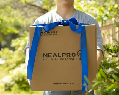 person carrying mealpro box box zoom background