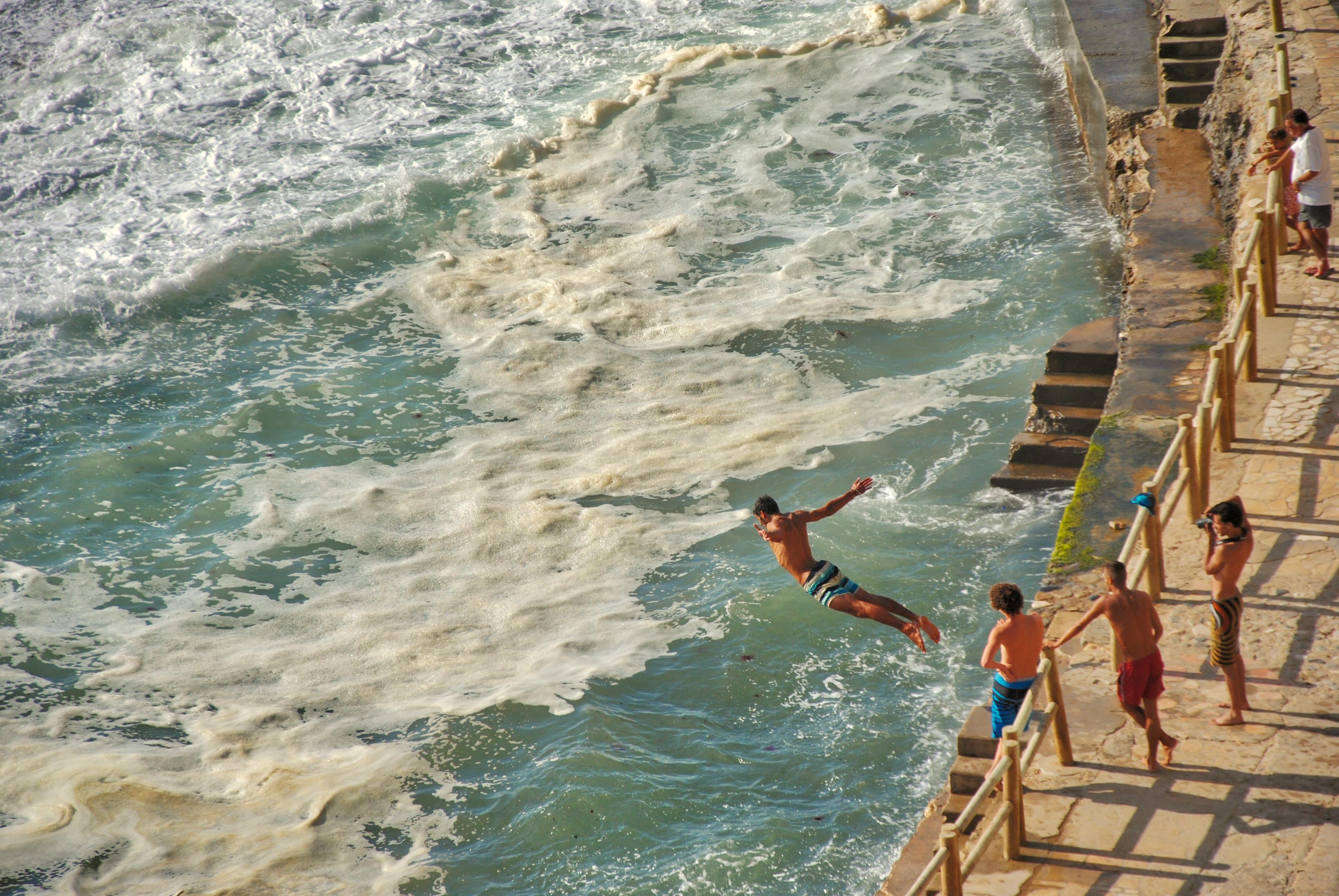 Man jumping on sea on focus photography. Azenhas do Mar, Portugal.