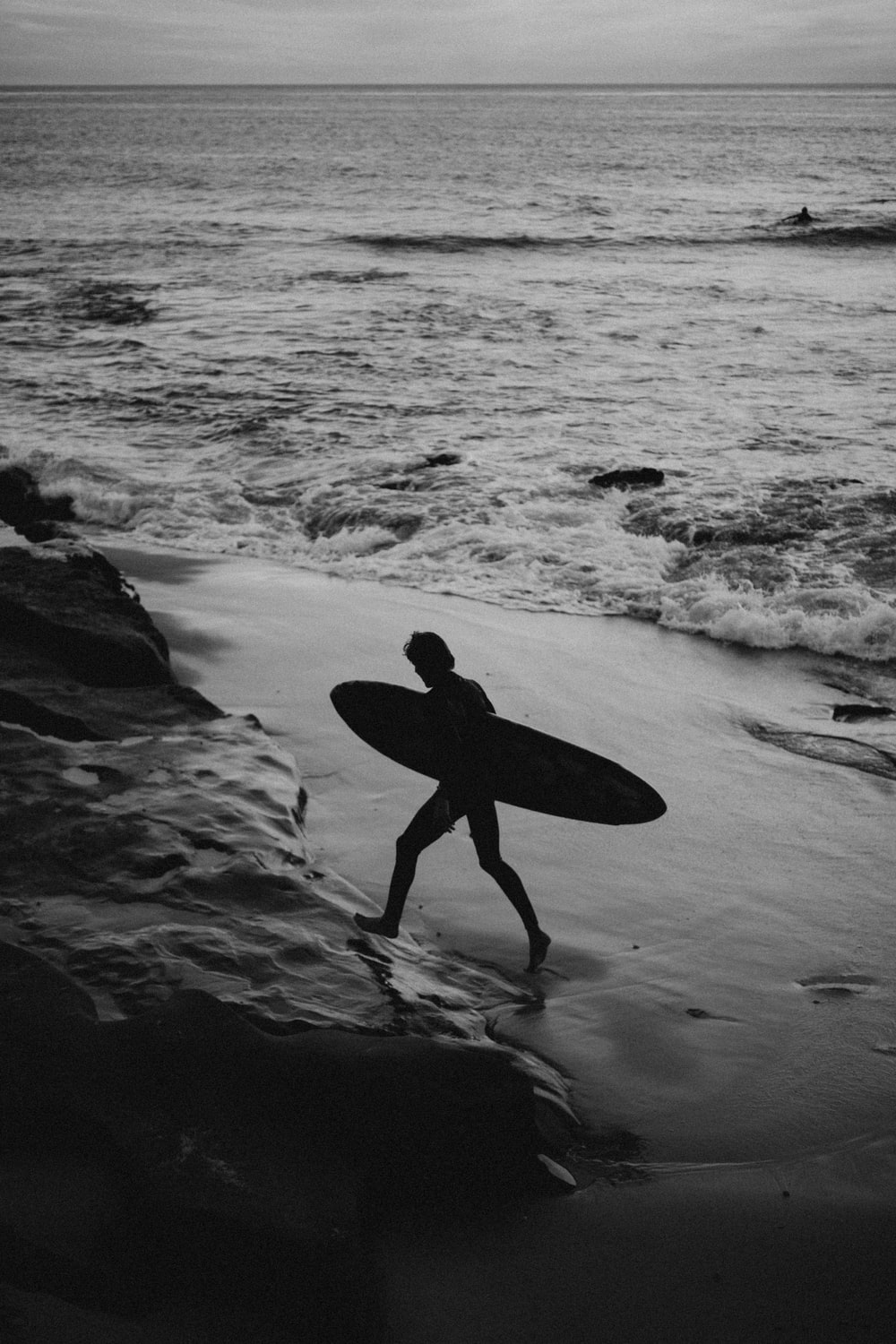 silhouette of man carrying surfboard