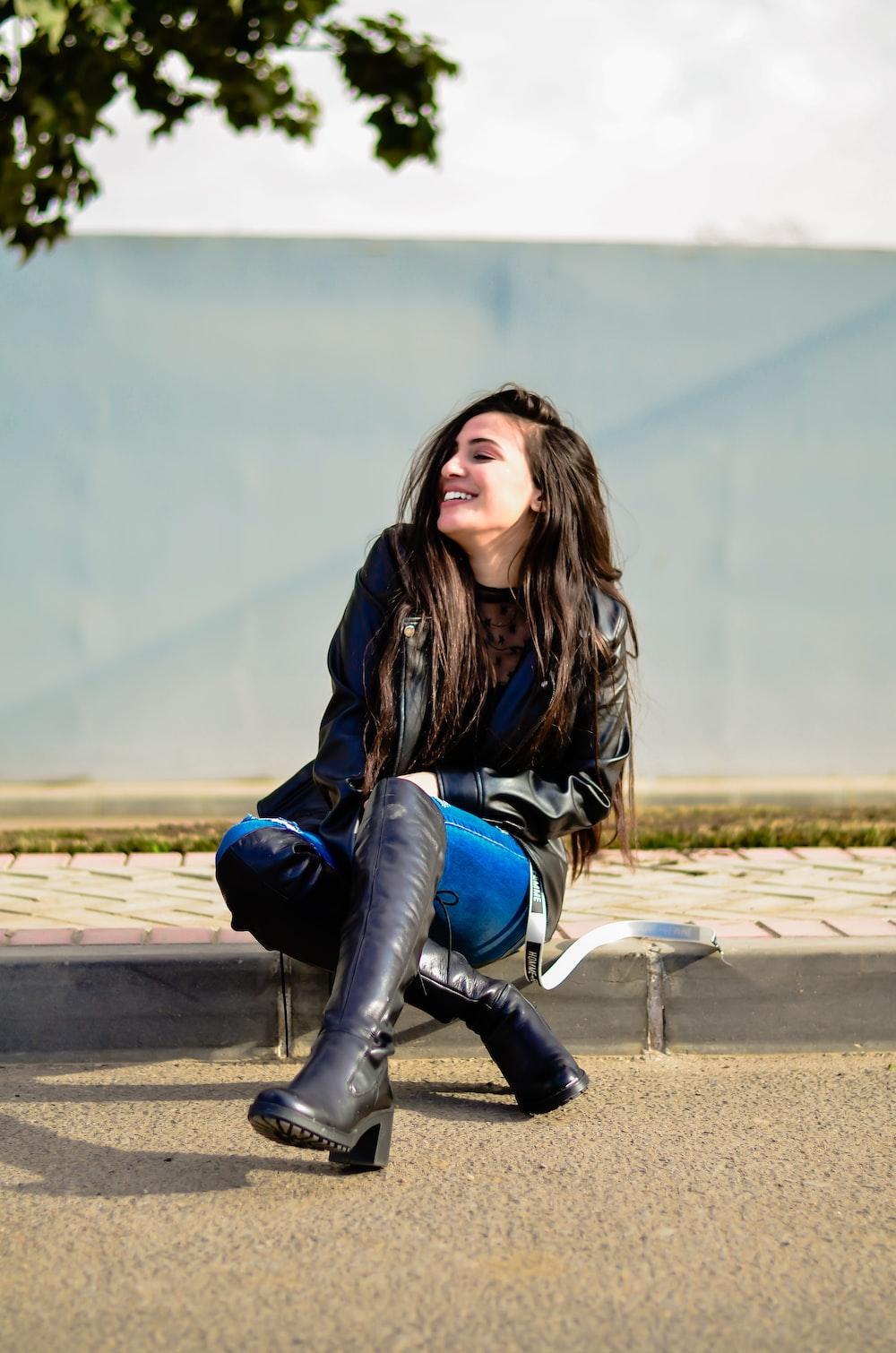 smiling woman sitting on pavement near tree