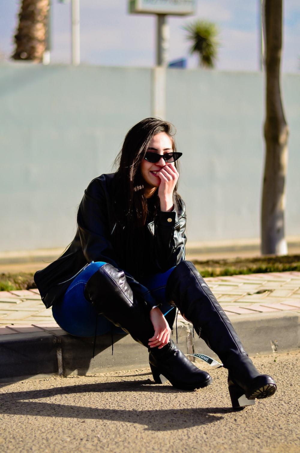 smiling woman sitting on pavement