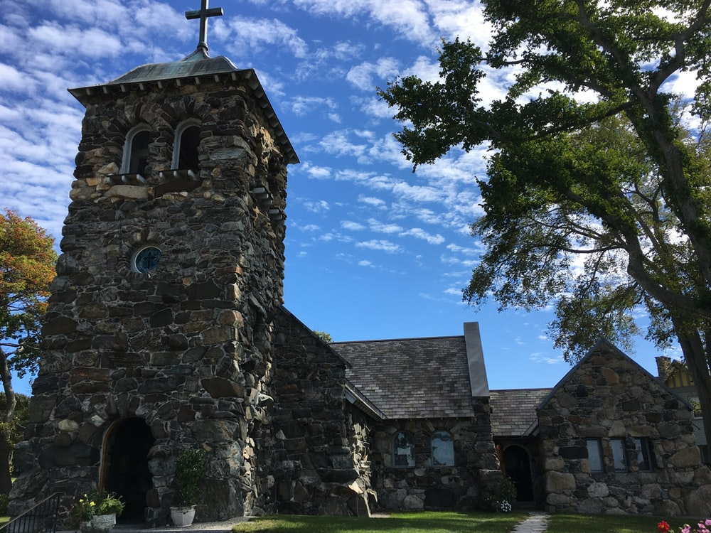 brown historic church near trees under blue and white sky during daytime