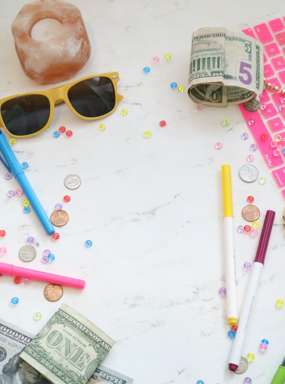 Marble money stock photo and money styled stock photo for personal finance bloggers, business coaches, and entrepreneurs with a pink keyboard, colorful pens, cash, and more.
