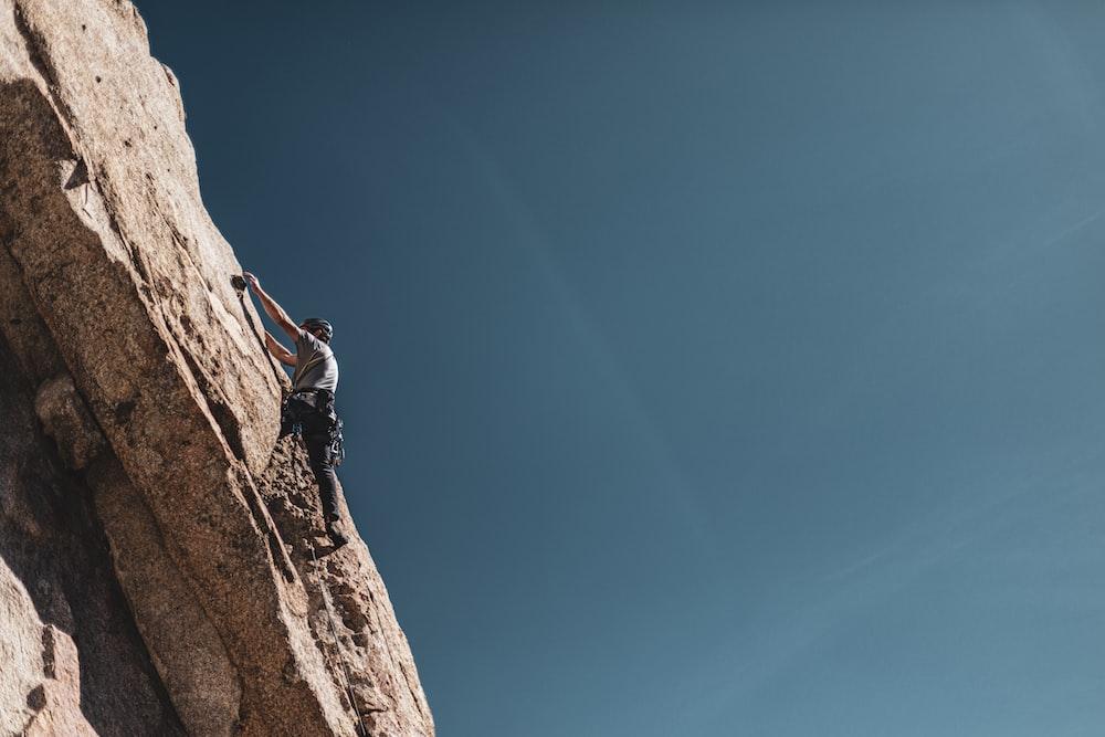 man climbing mountain during daytime