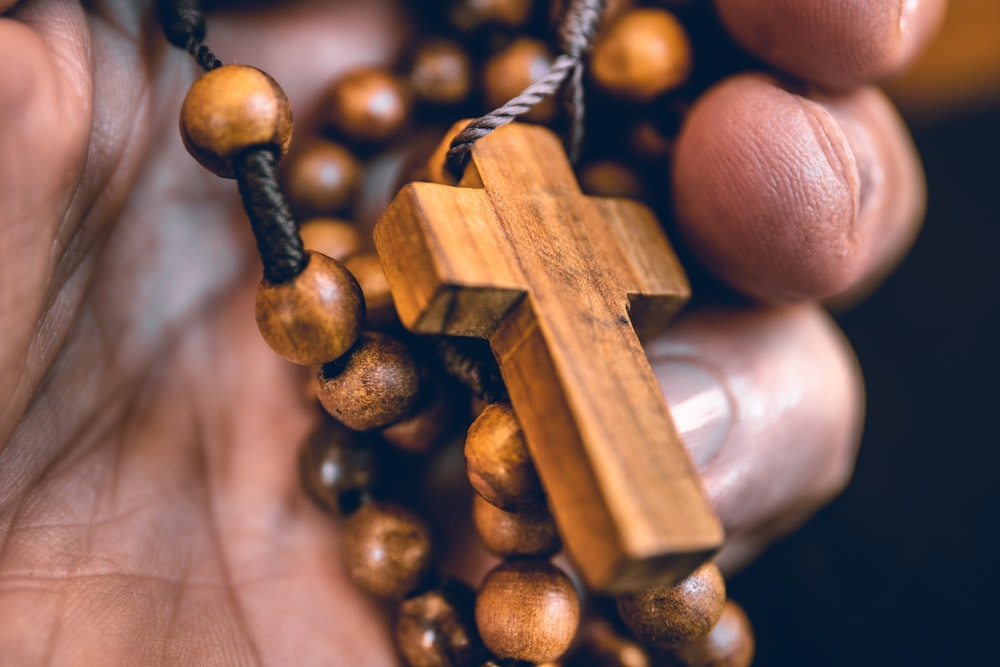 person holding beaded brown rosary