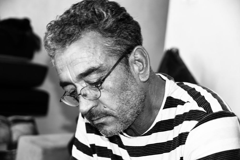 grayscale photography of man wearing eyeglasses and striped shirt