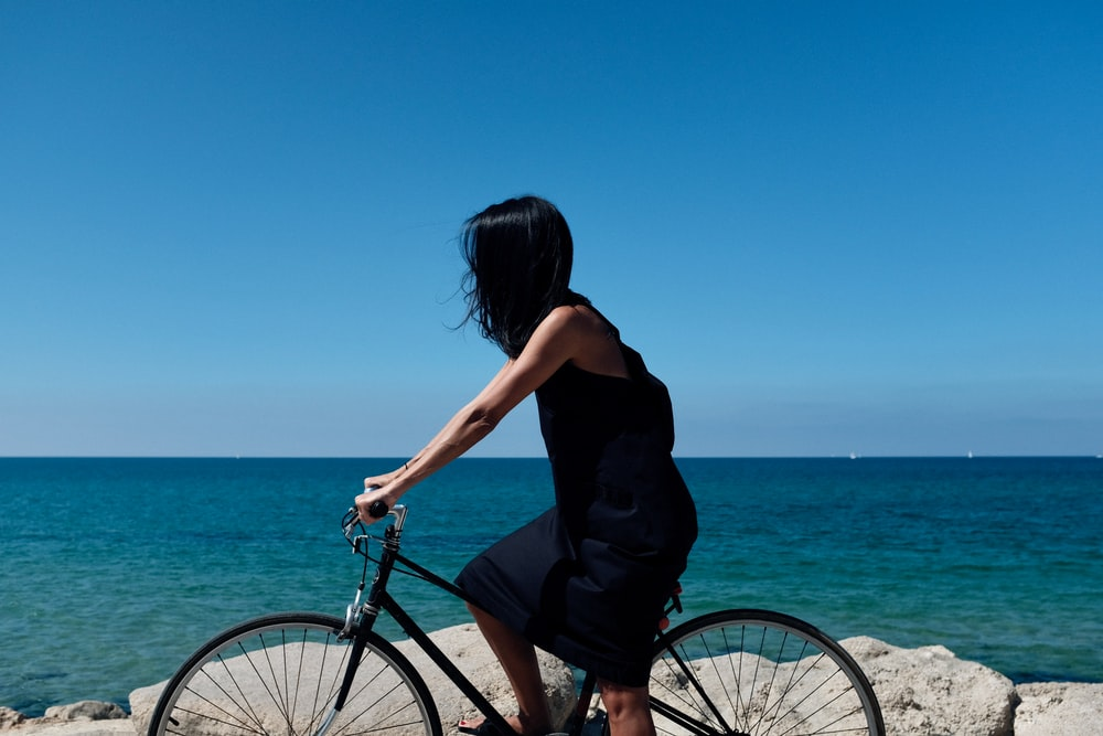 woman riding bicycle near body of water