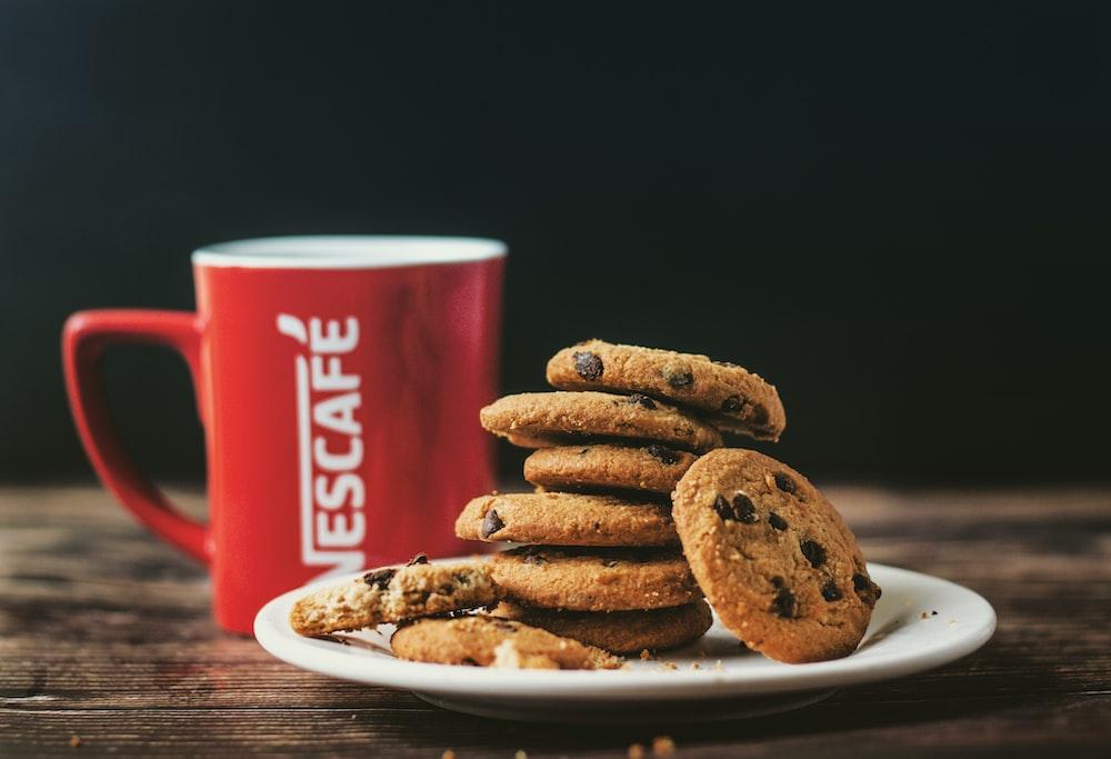 pile of cookies beside Nescafe ceramic mug