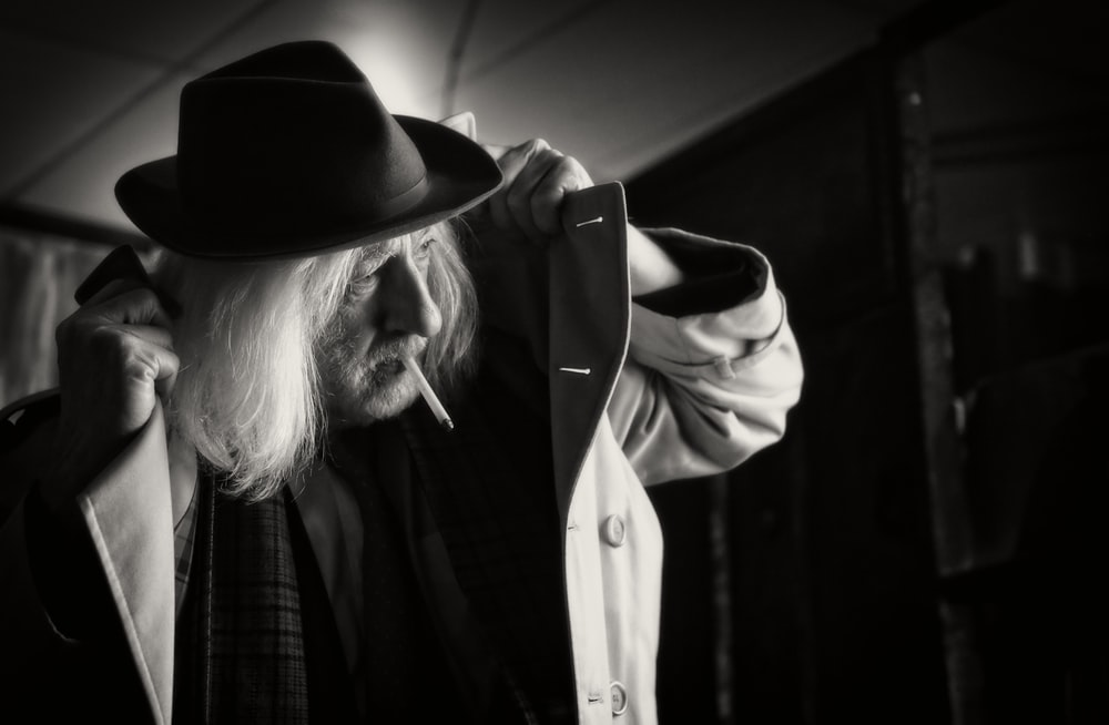 grayscale photography of man wearing hat and coat