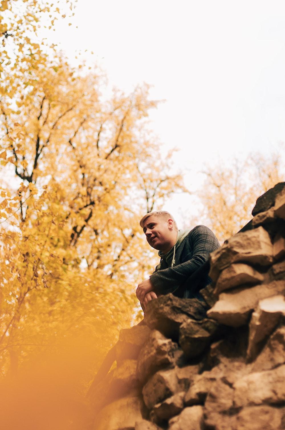 man wears black jacket sitting near yellow-leafed tree