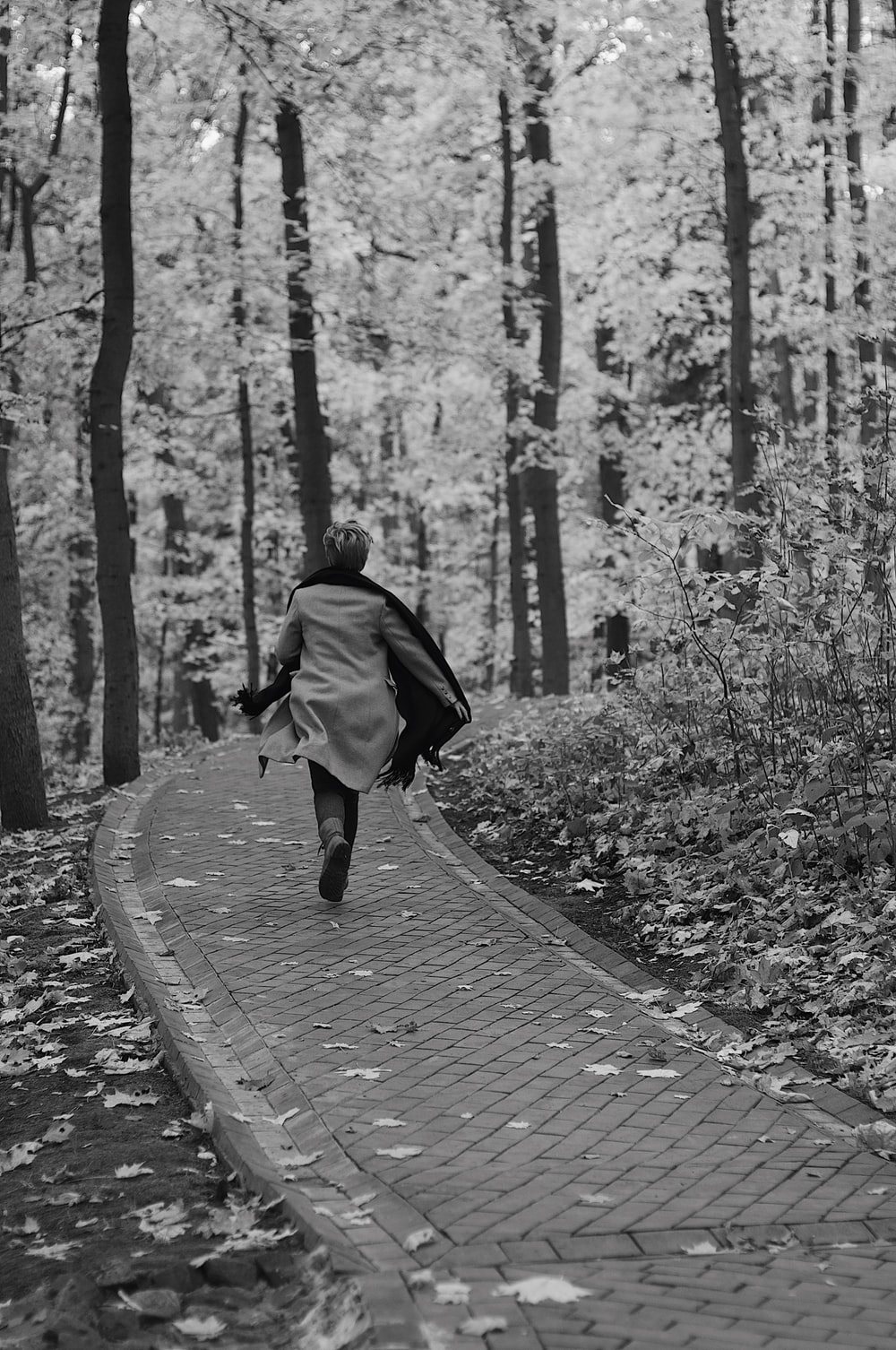 greyscale photography of running woman on pathway beside tres