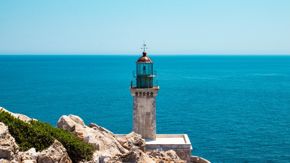 gray lighthouse under clear blue sky during daytime