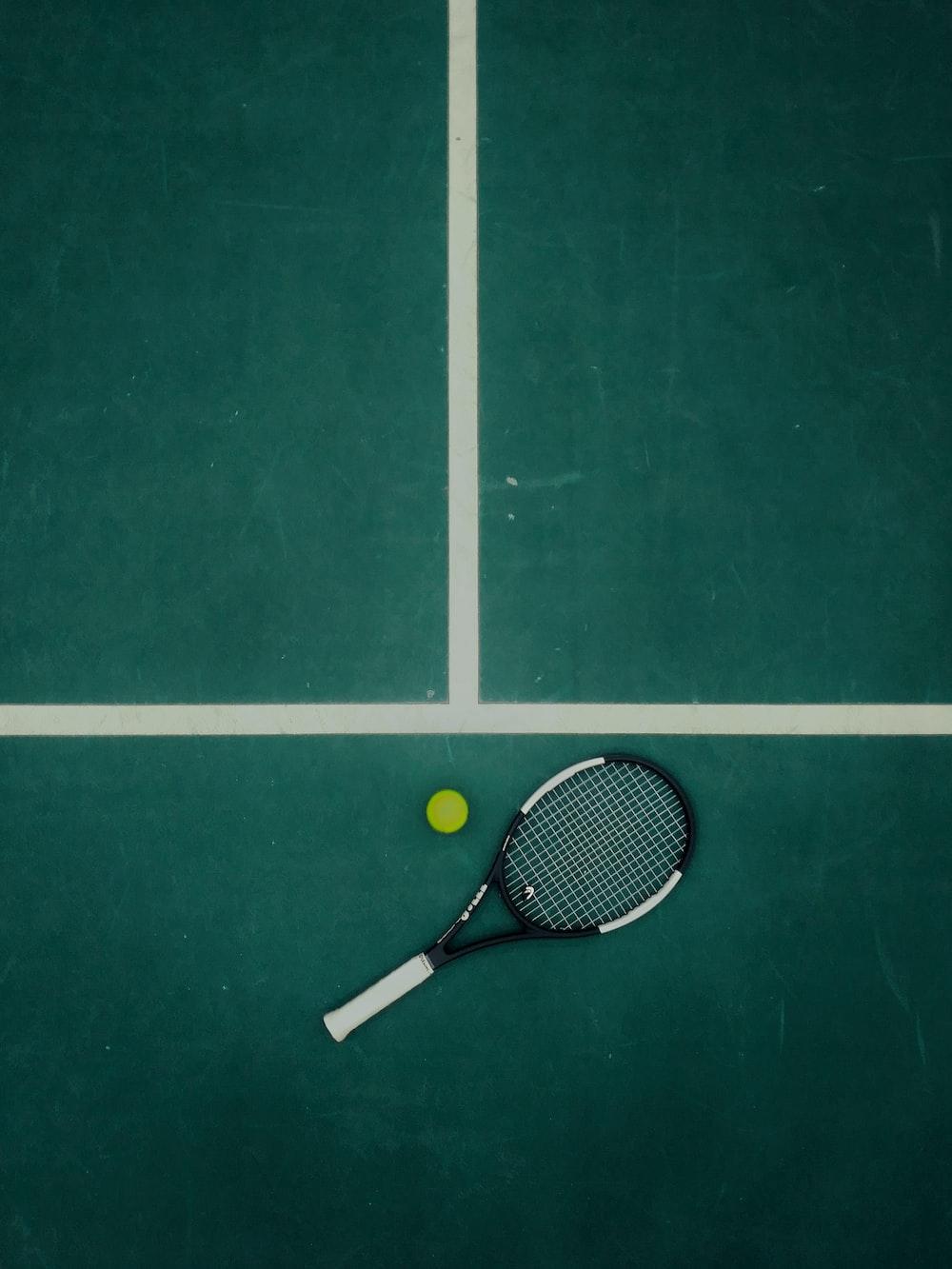 black and white tennis racket beside ball