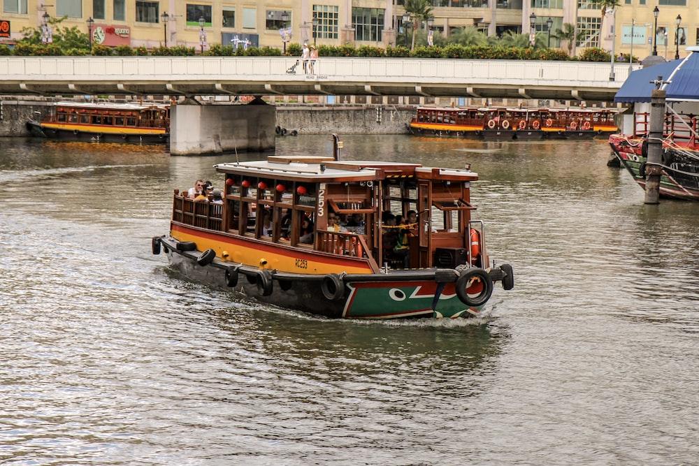 orange boat near bridge