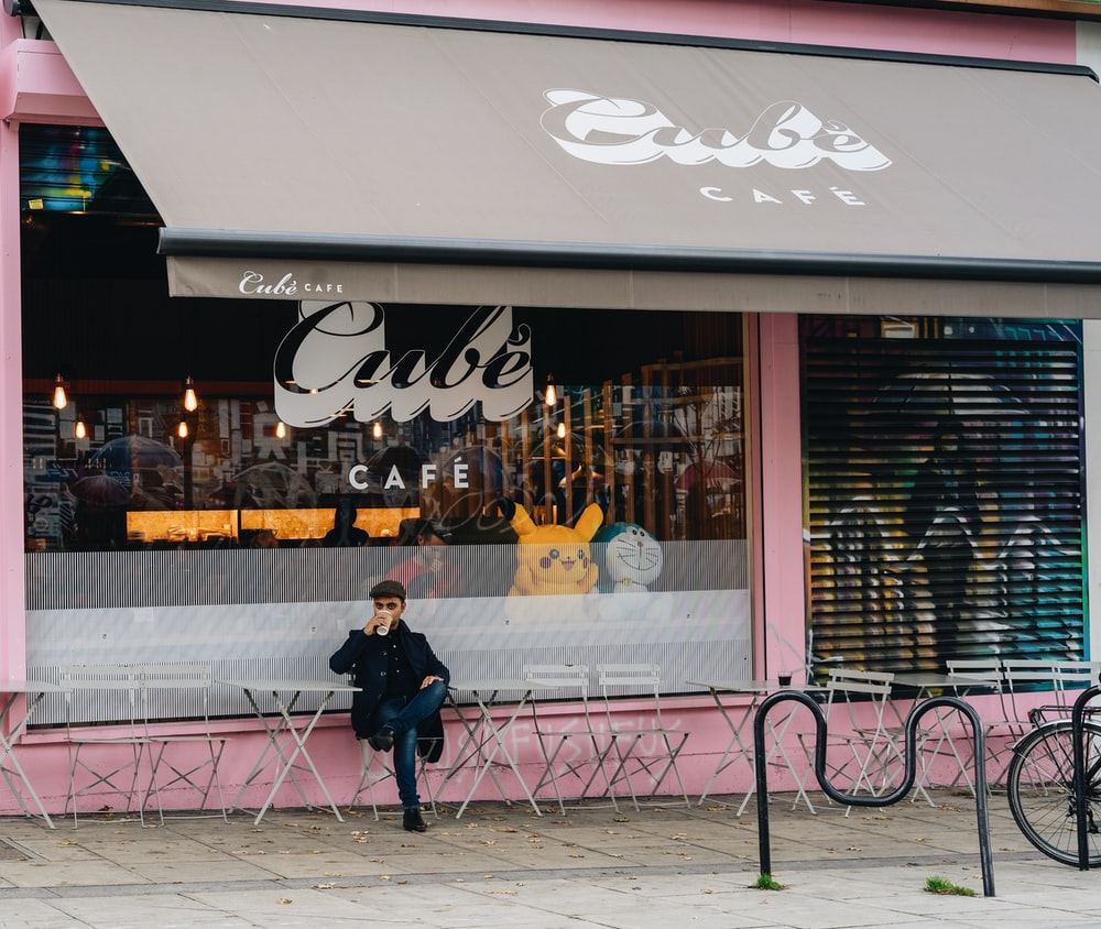 man sitting outside cafe while drinking coffe