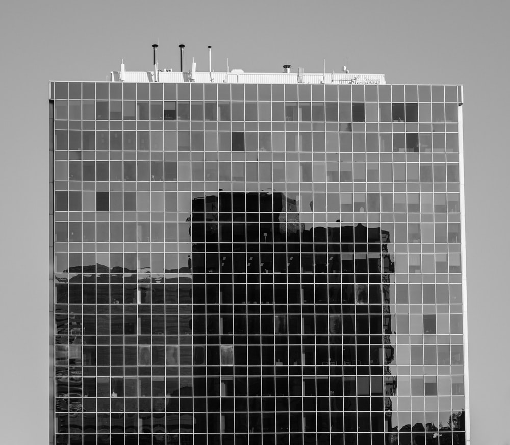 grayscale photography of glass walled building
