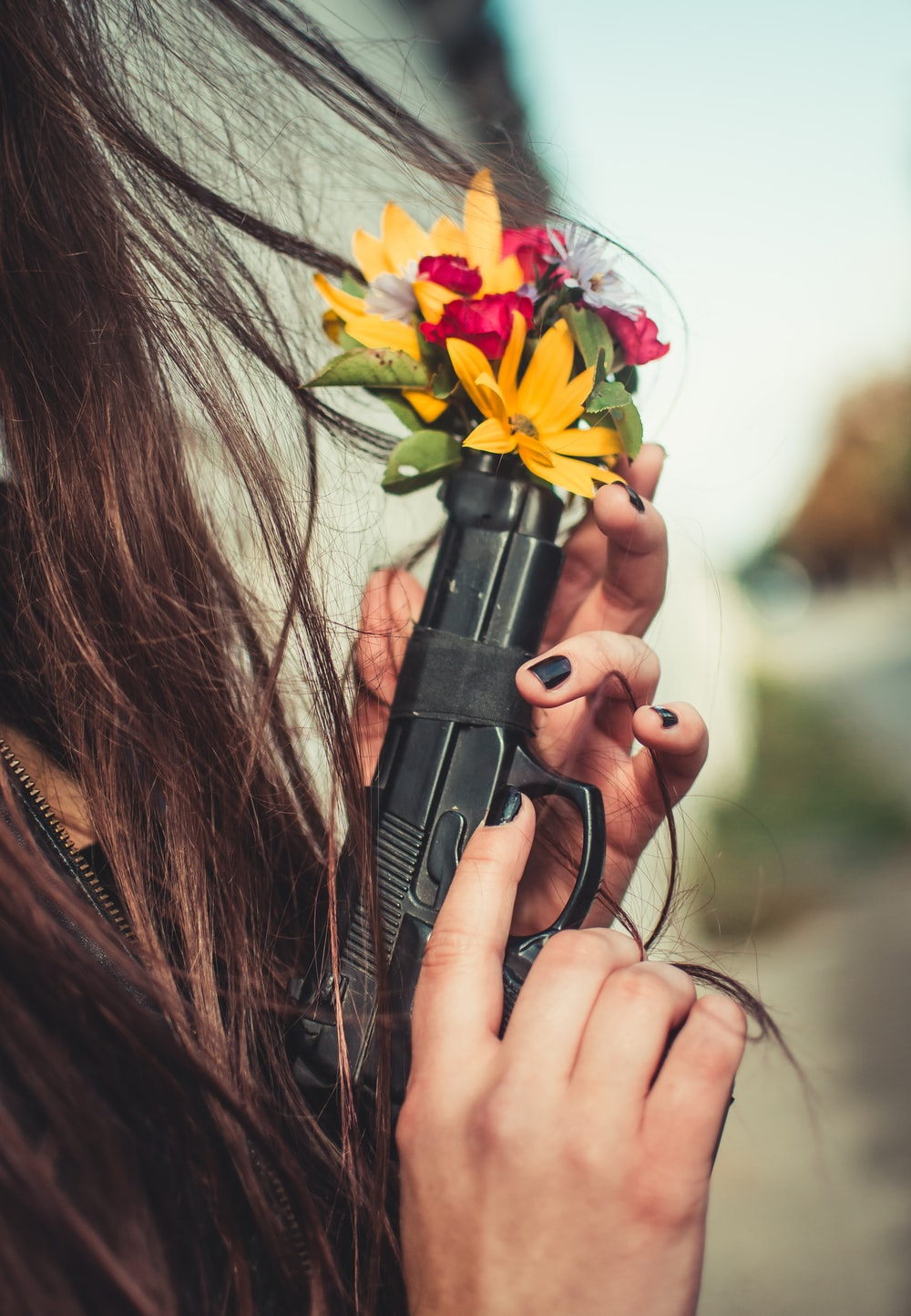 person holding automatic pistol with multicolored flowers on tip