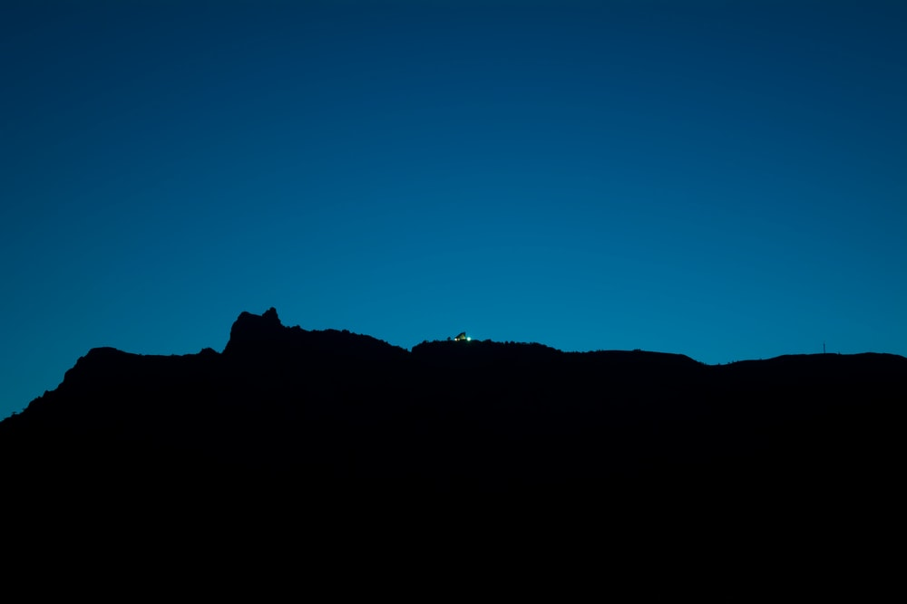 silhouette view of mountain on blue background