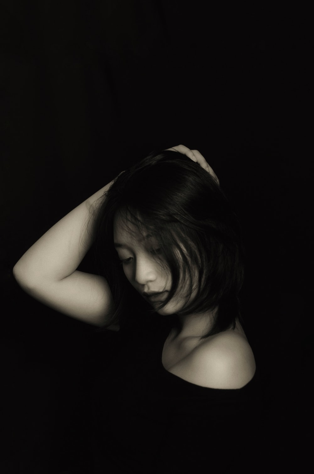 grayscale photography of woman wearing shirt touching her hair