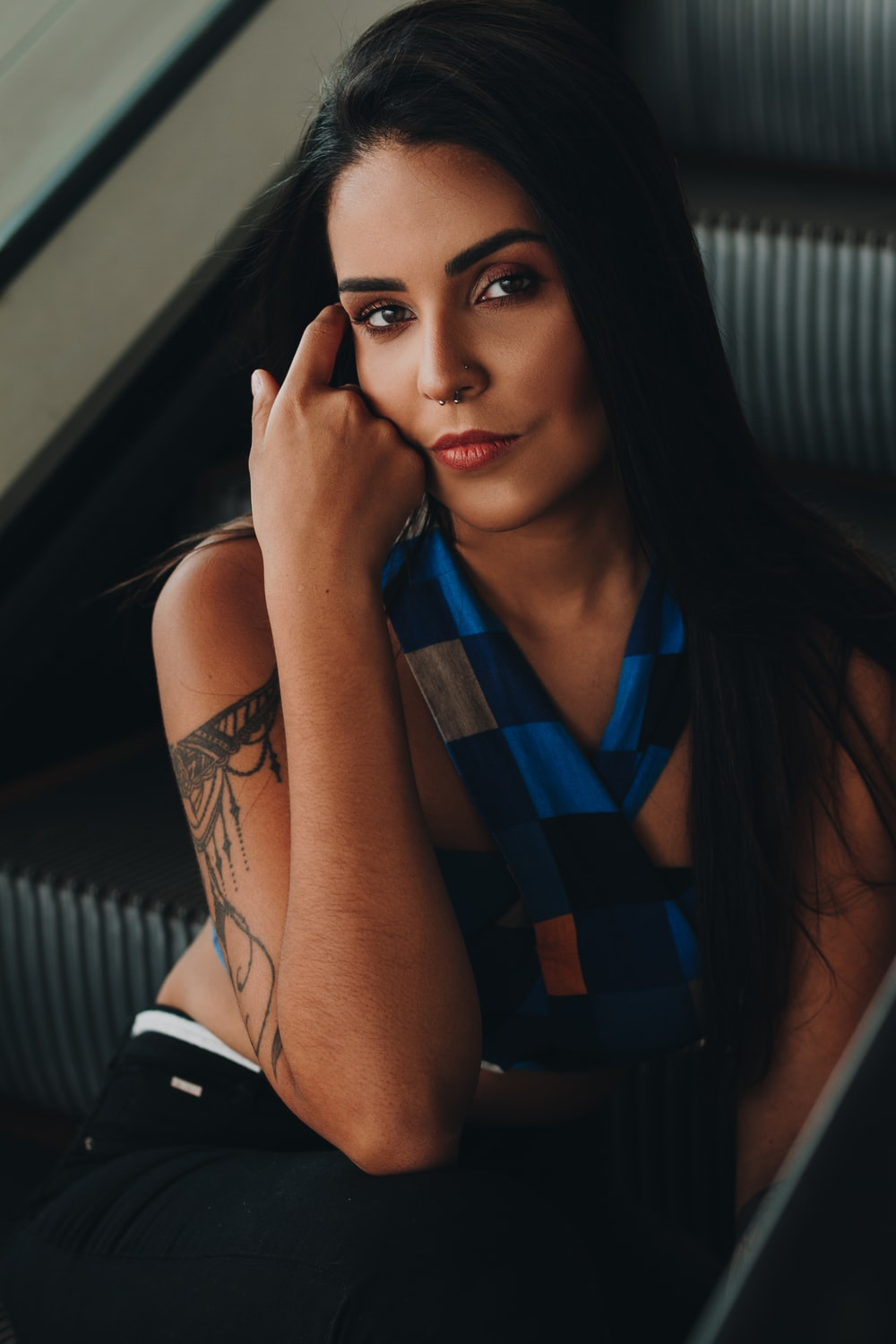 woman wearing blue and black halterneck top sitting and touching her face