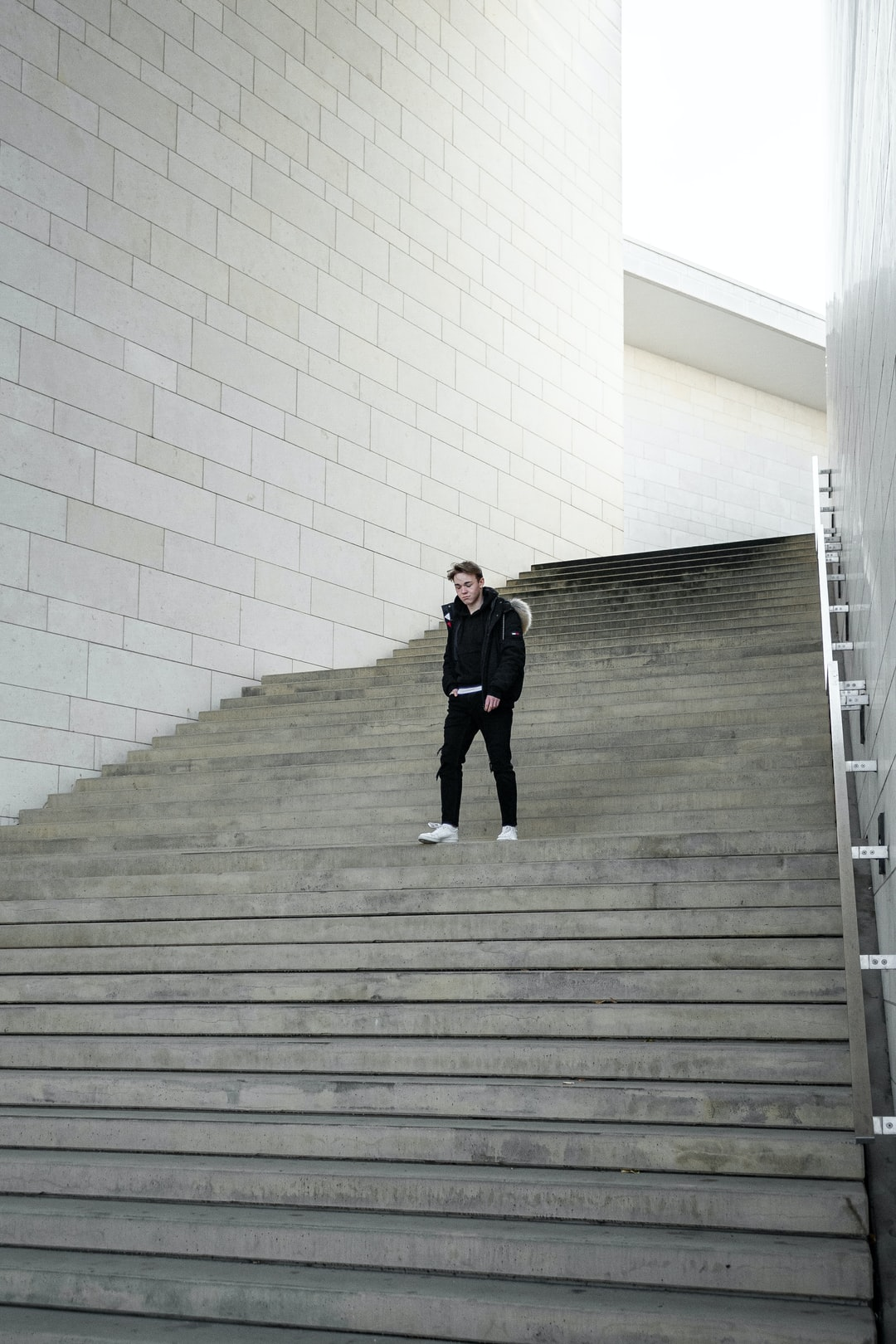 In this photo, Alex is wearing a black Stone Island hoodie together with black denim jeans, white Kenzo sneakers and a Tommy Hilfiger Jacket. This image was taken at Stadtkrone-Ost in Dortmund, Germany.
