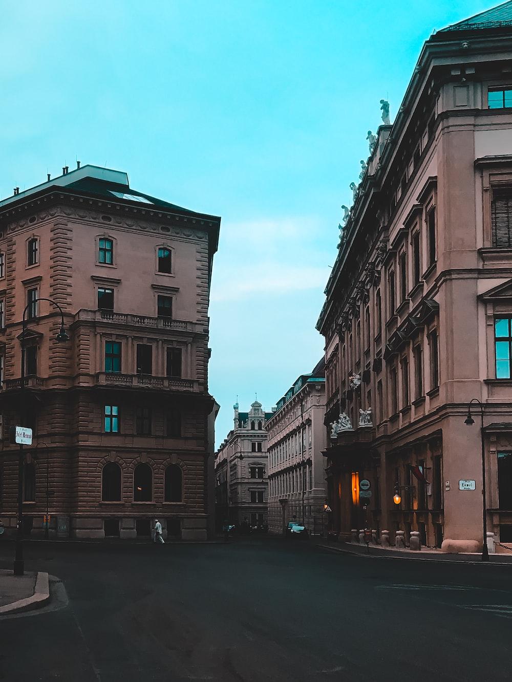 empty road between brown painted buildings