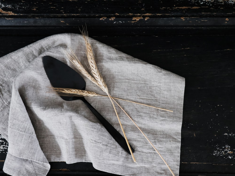 wheat grass and cake server on gray textile