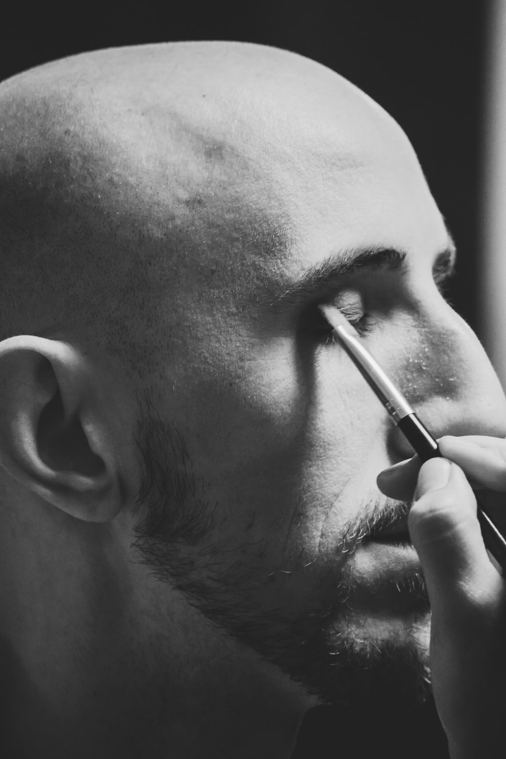 grayscale photo of person putting eyeshadow