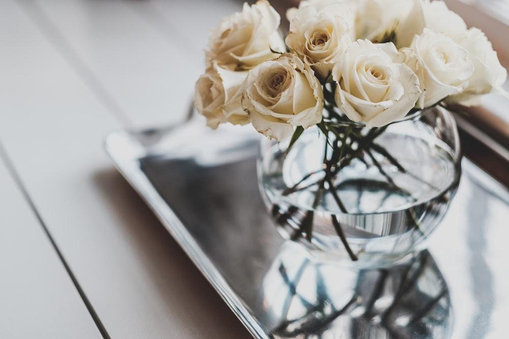 white rose arrangement on glass vase