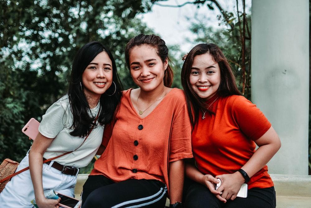 木の近くの3人の笑顔の女性