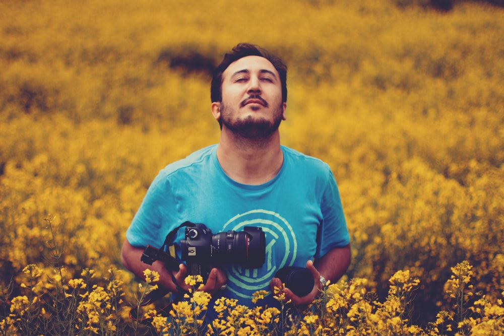 man wearing gray crew-neck shirt holding black DSLR camera standing in the middle of yellow flowers