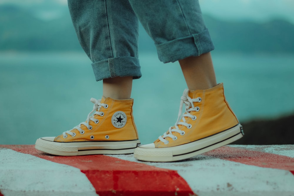 person wears yellow orange Converse All-Star high-top sneakers
