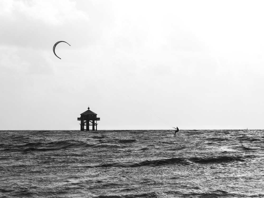 grayscale photo of person surfing on sea