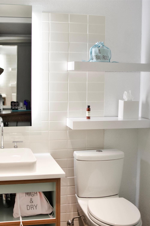 white ceramic toilet seat with white wooden shelf
