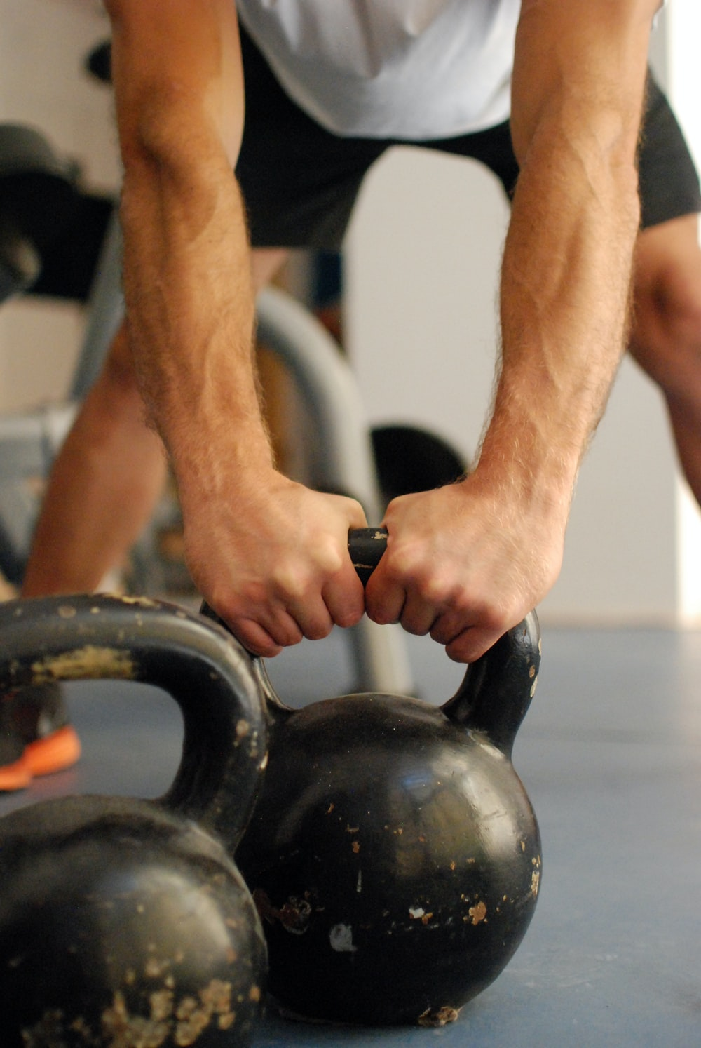 man standing and holding kettle bell