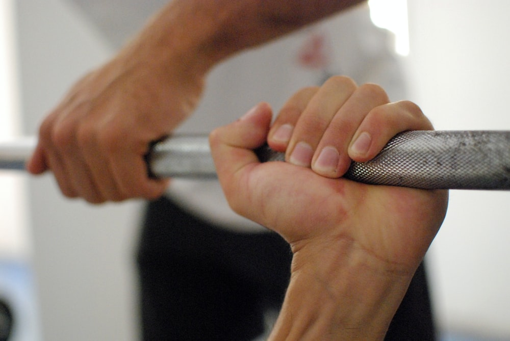 person holding barbell bar
