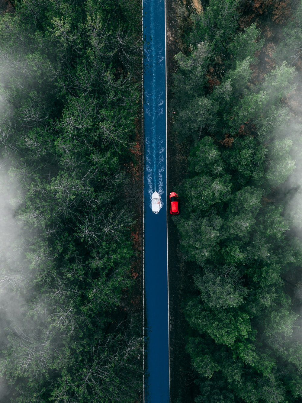 high angle photography of boat beside red vehicle