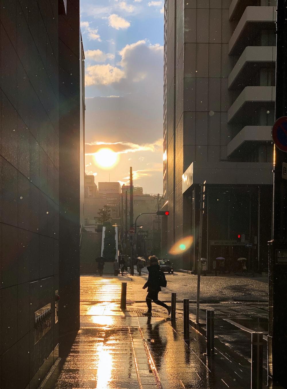 man walking near concrete buildings