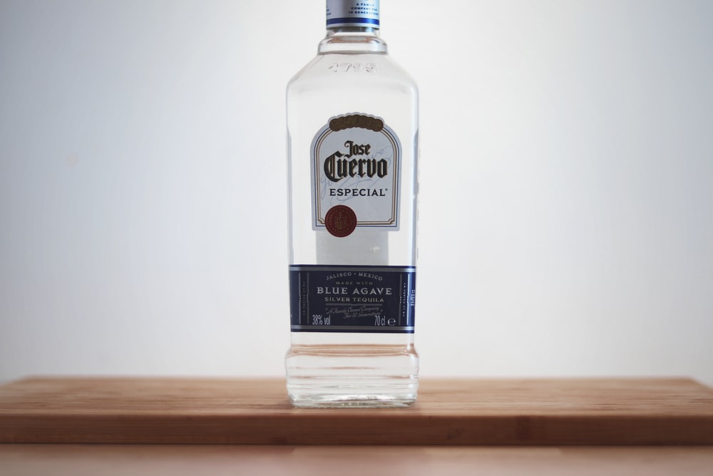Cuervo glass bottle on brown wooden surface