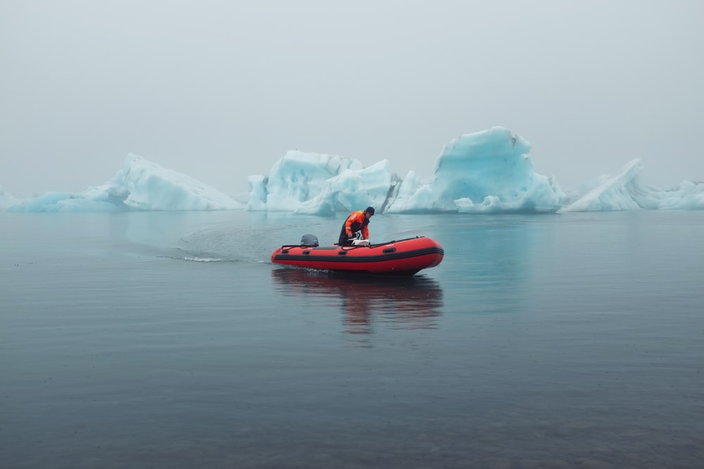 man riding inflatable boat near icebergs