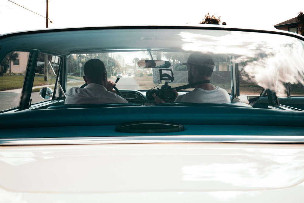 two men sitting in vehicles