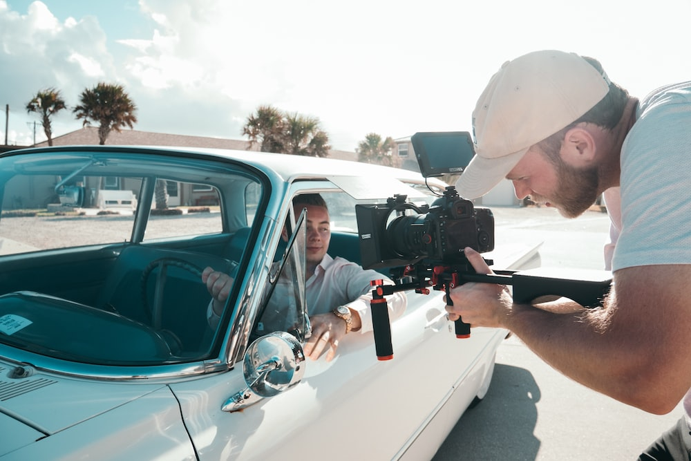 man holding camera filming another man in car