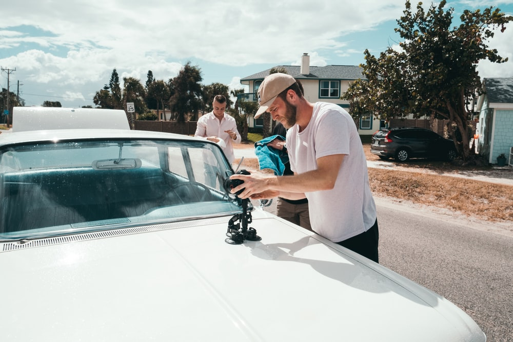 man holding camera on white car