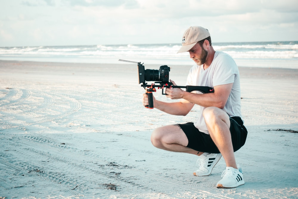 man holding camera on shore