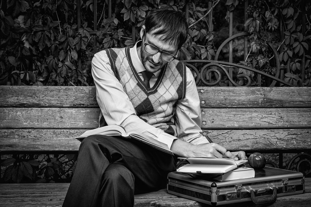 grayscale photo of man in sweater vest sitting on bench
