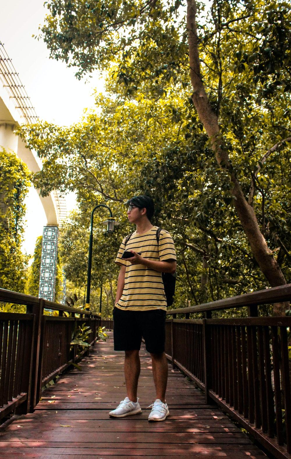 standing man wearing black and yellow striped shirt beside tree