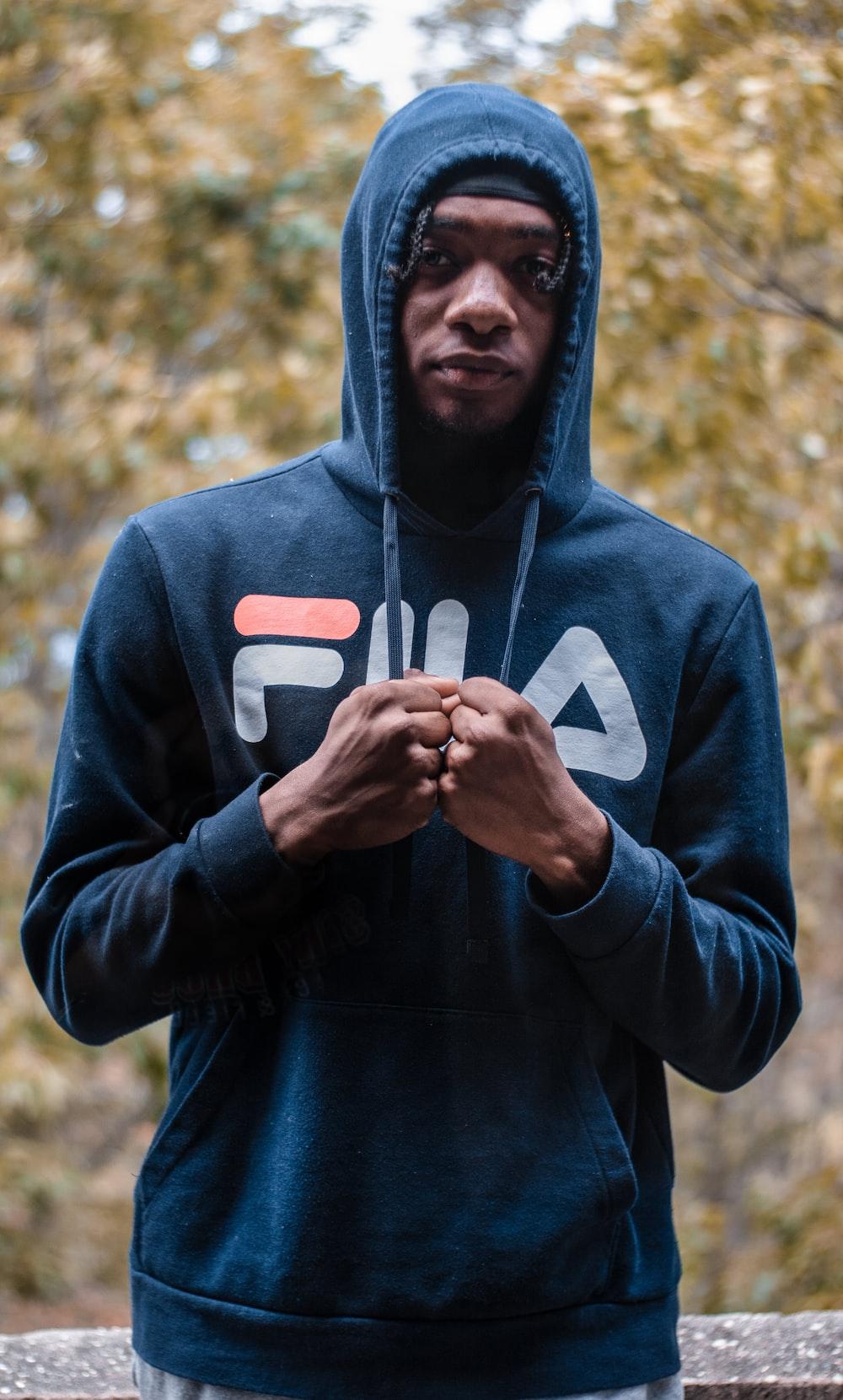 man wearing blue Fila pullover hoodie